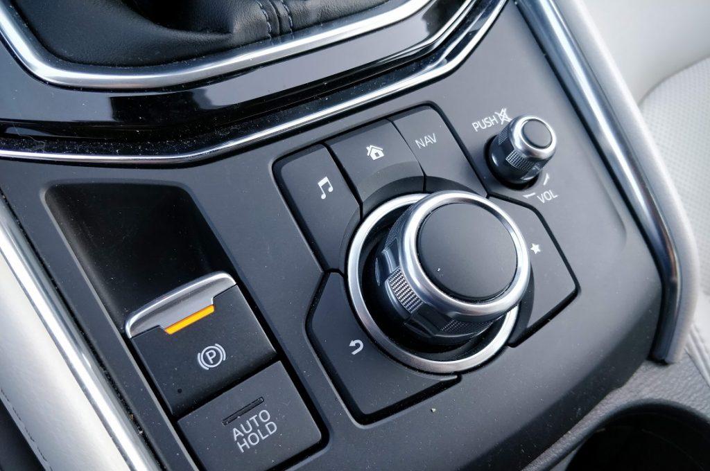 Detalle del conjunto de mandos del sistema MZD- Connect situado entre los asientos delanteros