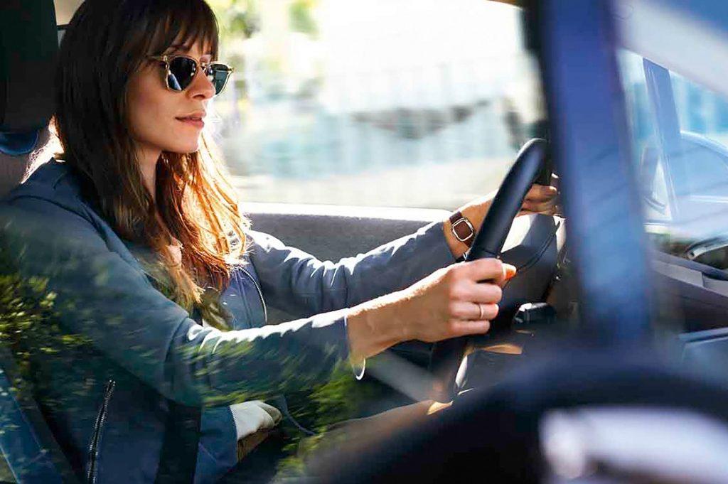 Mujer hermosa al volante de un vehículo BMW.
