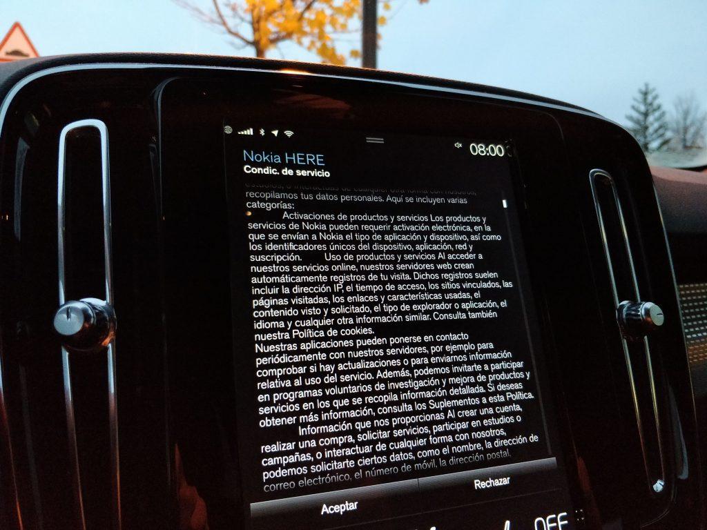 volvo xc40 detalle de la pantalla de la consola central en posición vertical con indicaciones de la letra pequeña del servicio Nokia Here