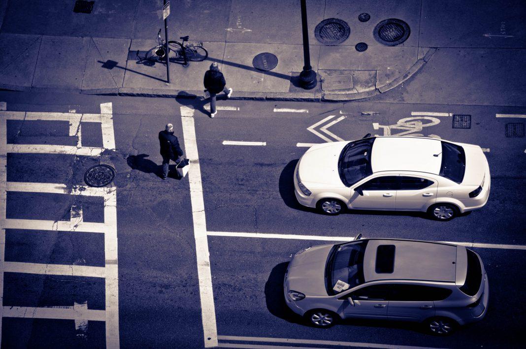 Vista superior de un paso de peatones. Una persona lo está cruzando y dos coches están parados, esperando