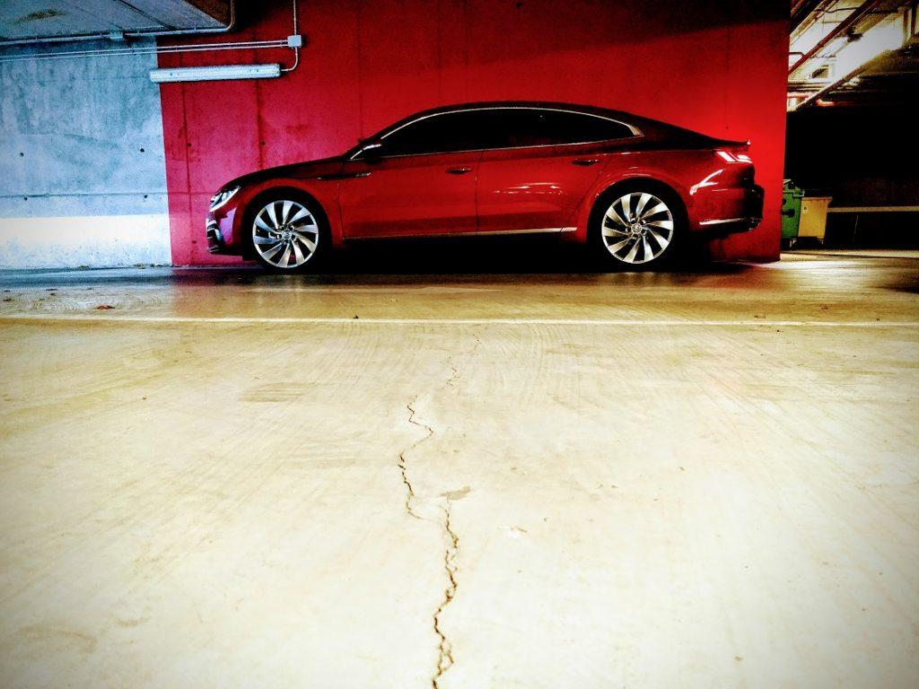 Imagen de un Volkswagen Arteon de color rojo en un garaje con una pared roja de fondo