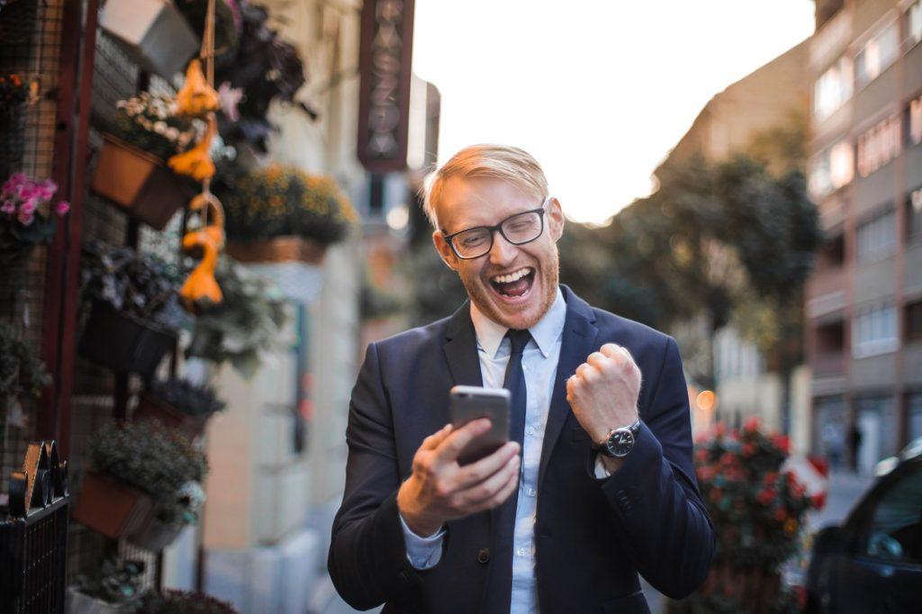 UNa persona sostiene su teléfono móvil con cara alegre