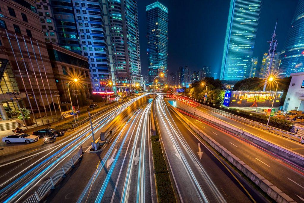 Imagen de una carretera que atraviesa una ciudad de noche repleta de luces