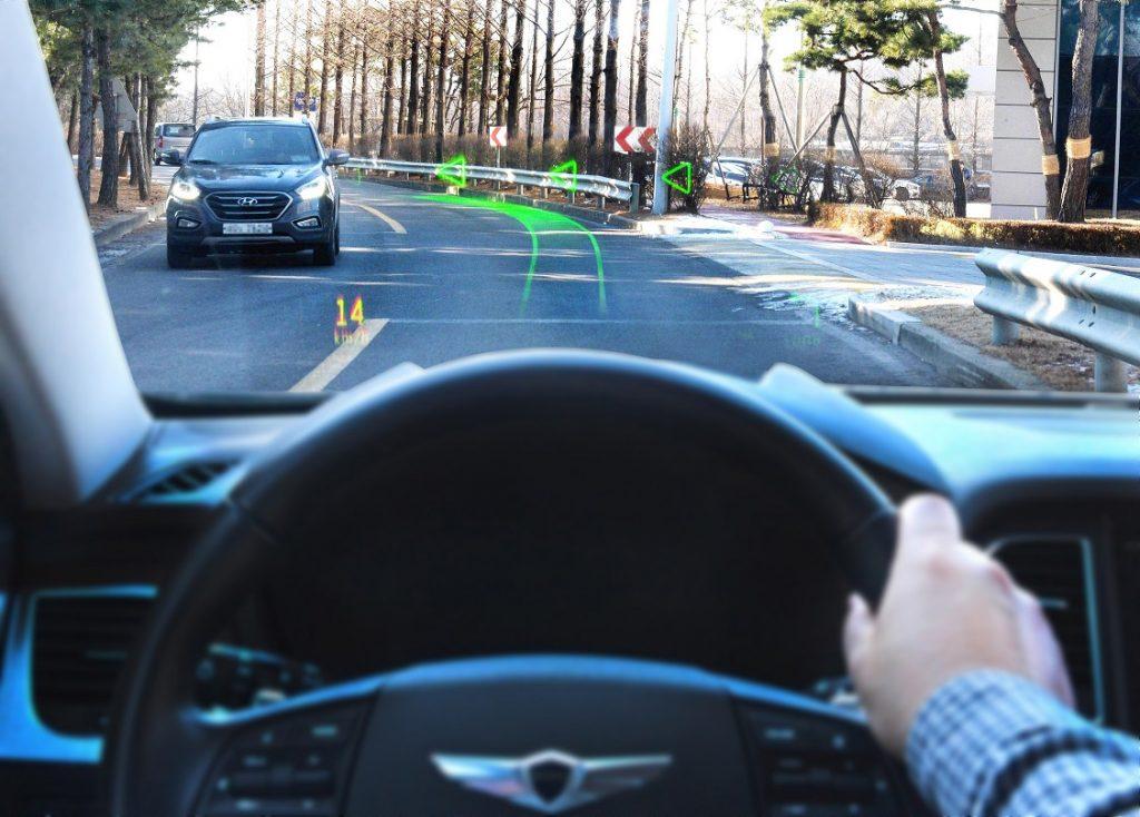 A través de un parabrisas de realidad aumentada se ve la carretera y sobreimpresa en ella las señales del navegador