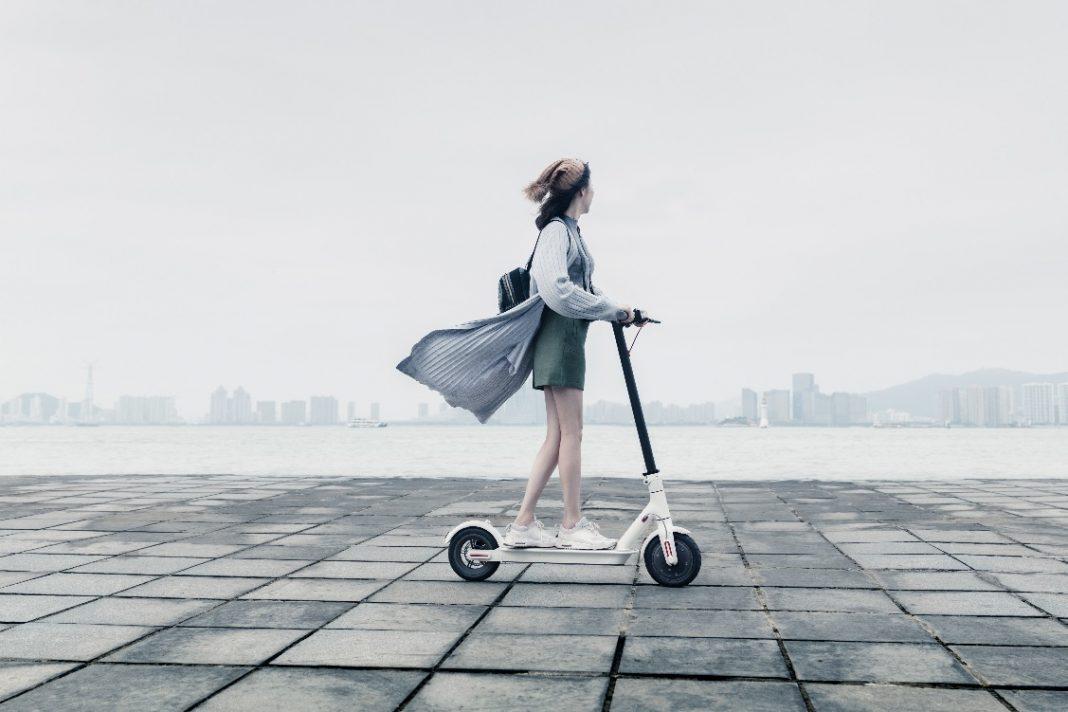 Hermosa chica china con un Mi Electric Scooter de Xiaomi
