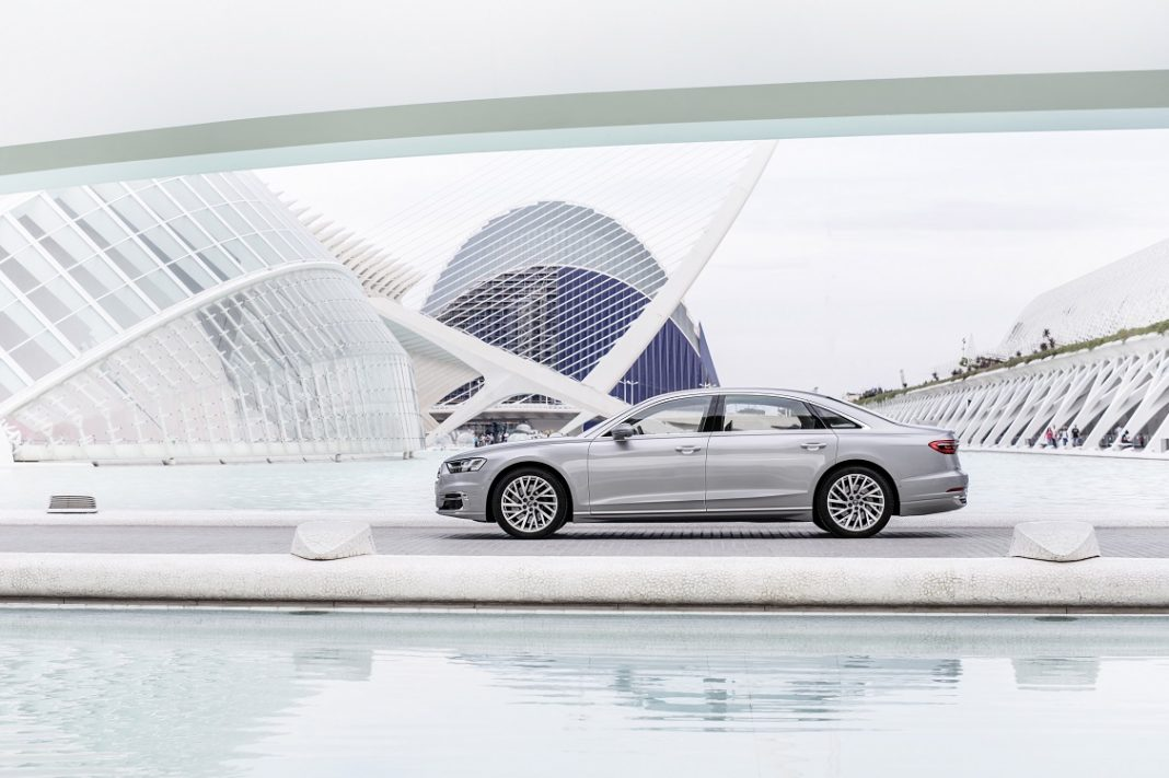 Audi A8 de color plateado, foto de perfil con el coche posando en la ciudad de las artes y las ciencias