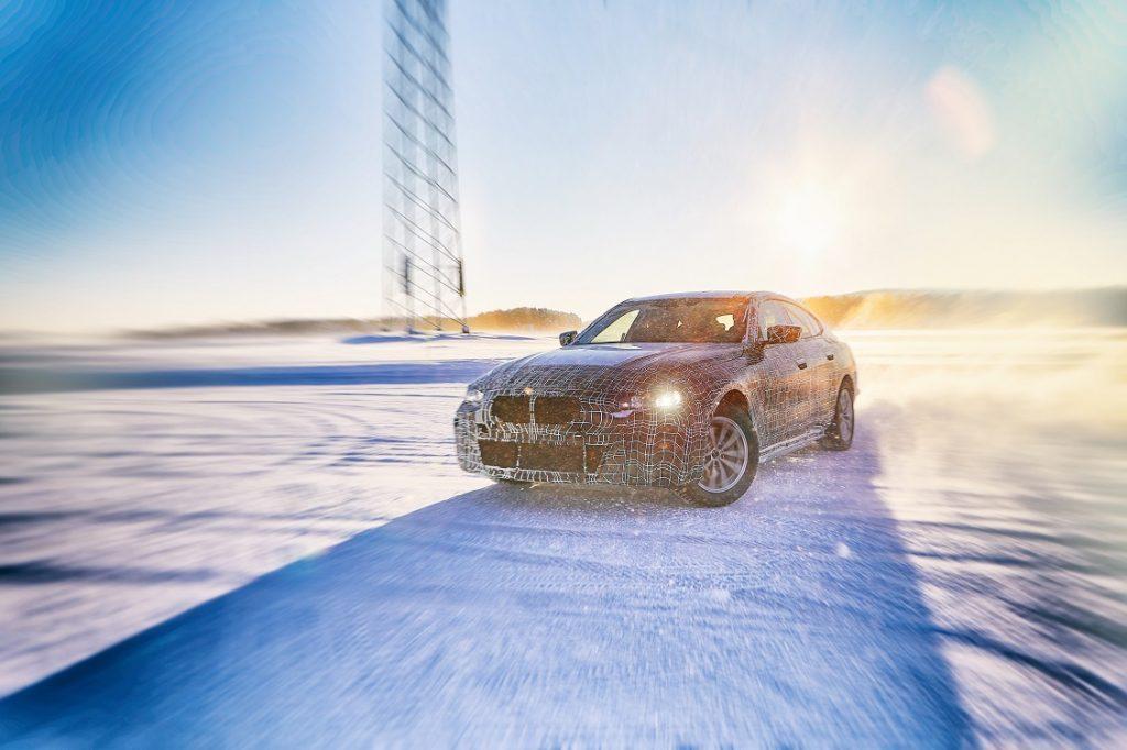 Foto de tres cuartos delantero del BMW i4 circulando por una carretera nevada