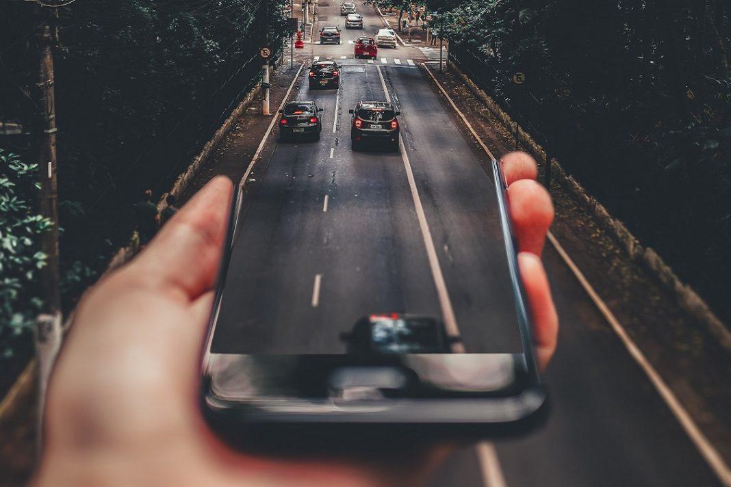 Imagen creativa en la que un teléfono móvil se ve extendido, convirtiéndose en una carretera por la que circulan varios vehículos