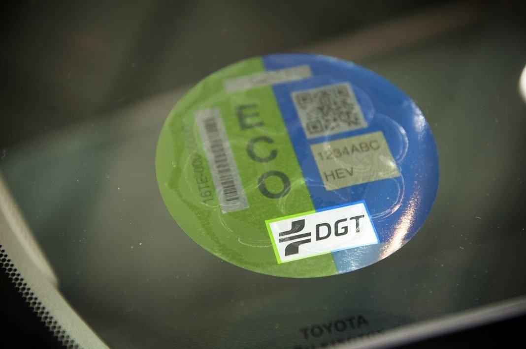 Detalle de una etiqueta ECO de la DGT situada en el parabrisas de un coche