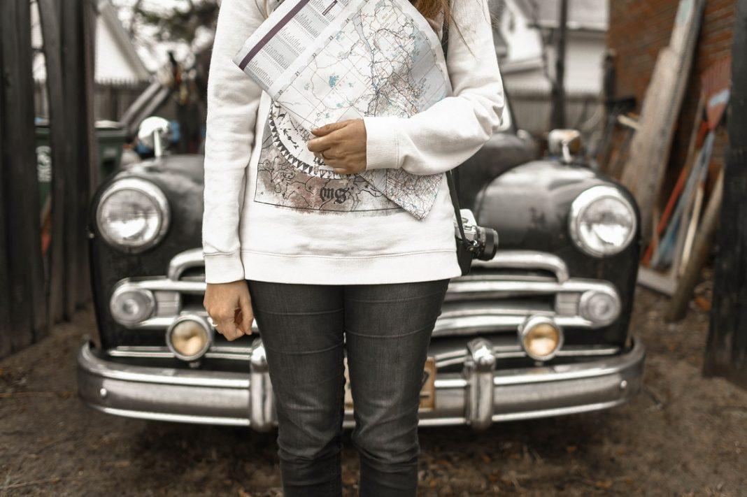 Una mujer posa de pie frente a un coche clásico