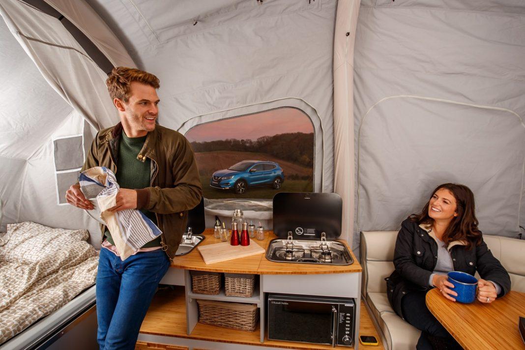 Imagen de una pareja dentro de una tienda de campaña dotada de todas las comodidades