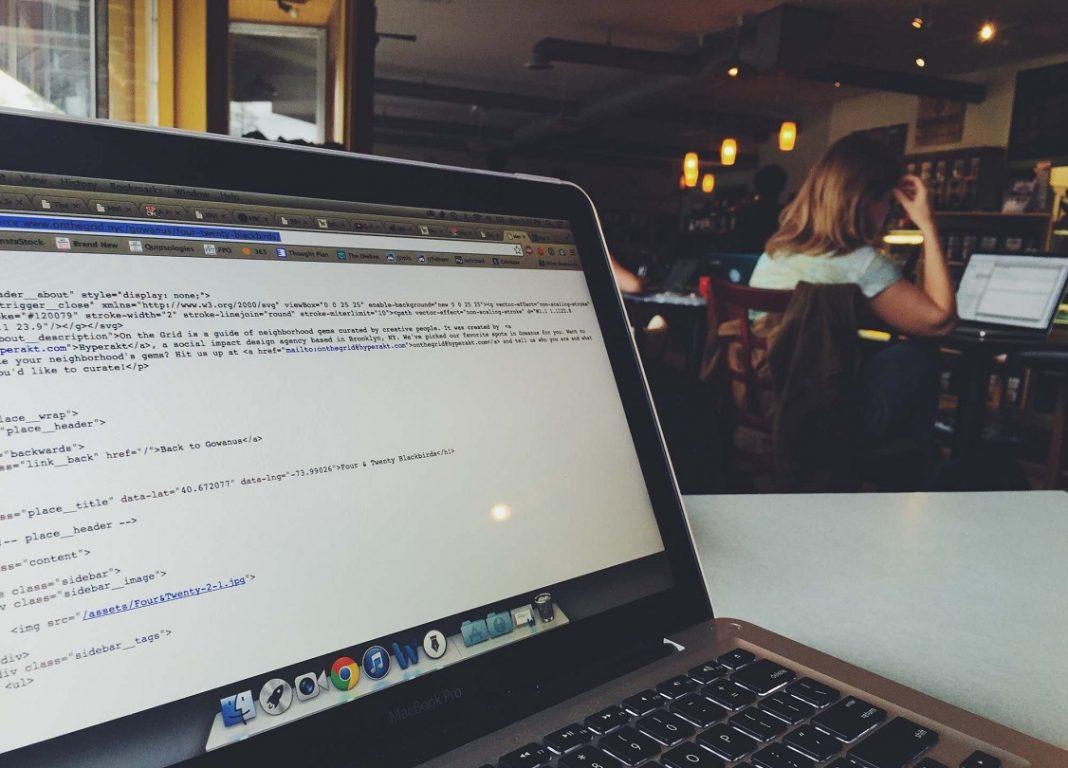 Imagen de un portátil sobre la mesa de una biblioteca sin nadie que lo controle