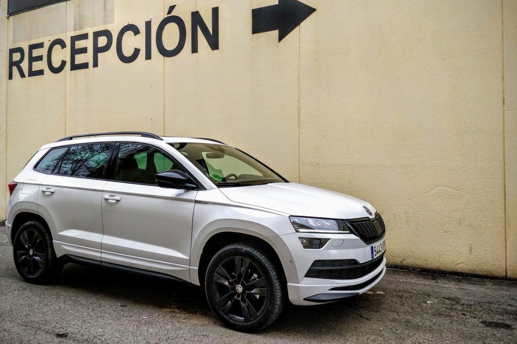 Imagen de Skoda Karoq blanco aparcado en tres cuartos delantero delante de una pared en la que pone Recepción