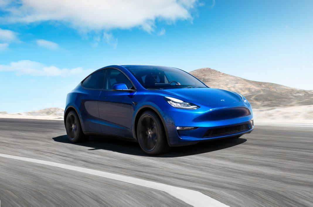Tesla Model Y color azul oscuro en tres cuartos delantero circulando por carretera