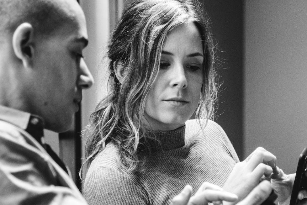 Una mujer y un hombre miran las pantallas de sus teléfonos