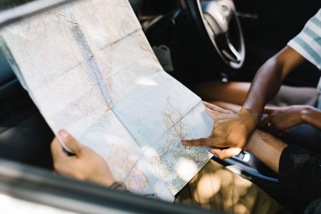 Dos personas consultan un mapa dentro de un coche.