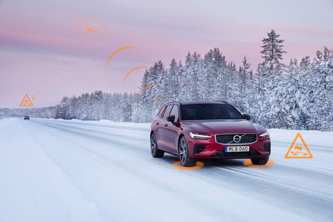 Imagen de un Volvo V60 de color rojo sobre una carretera nevada y enviando una señal de alerta
