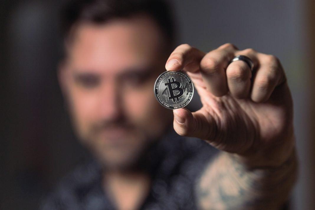 Hombre sujetando en la mano un Bitcoin