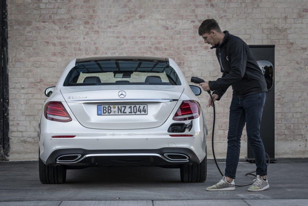UNa persona conecta el enchufe para recargar un Mercedes híbrido enchufable