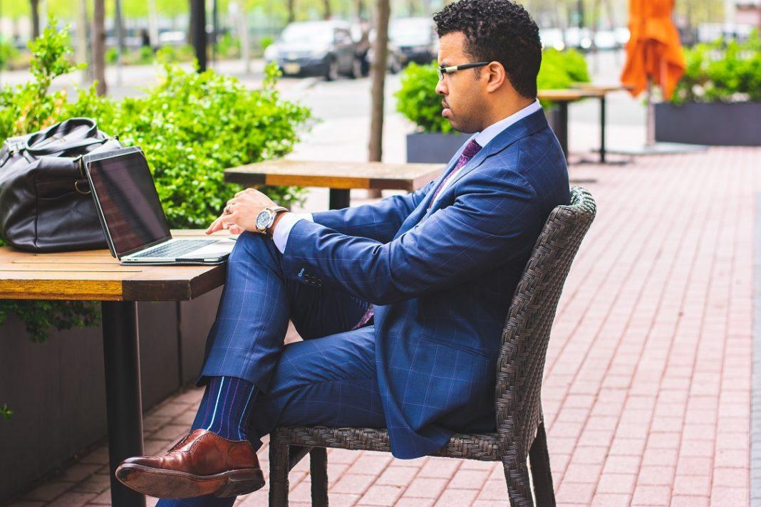 Hombre sentado en la terraza de un café usando su portátil