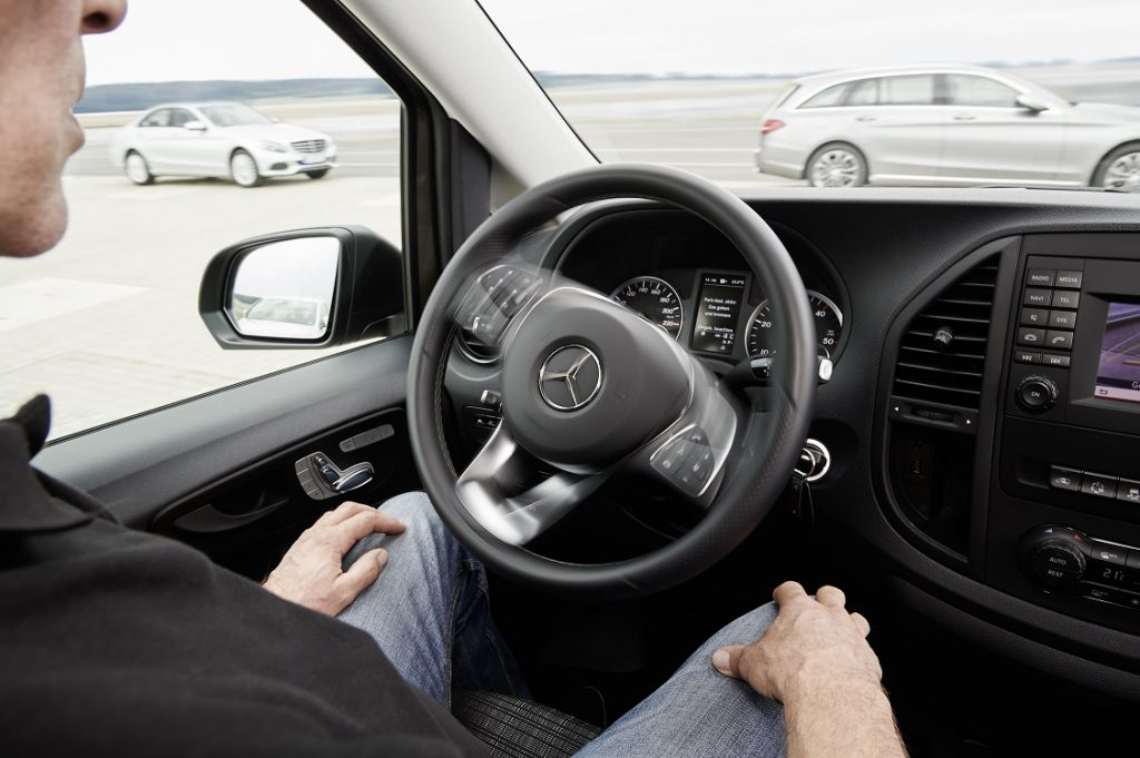 UNa persona está al volante de un coche que realiza solo la maniobra de aparcar