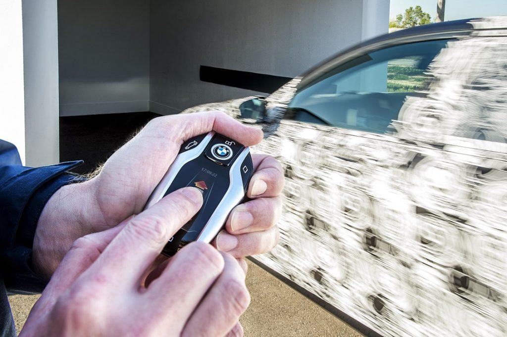 Una persona utiliza el mando a distancia del vehículo para aparcar el coche