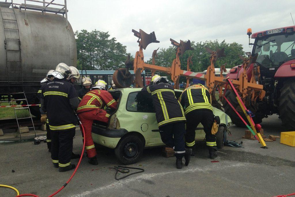 Imagen de un grupo de bomberos haciendo un simulacro con un coche
