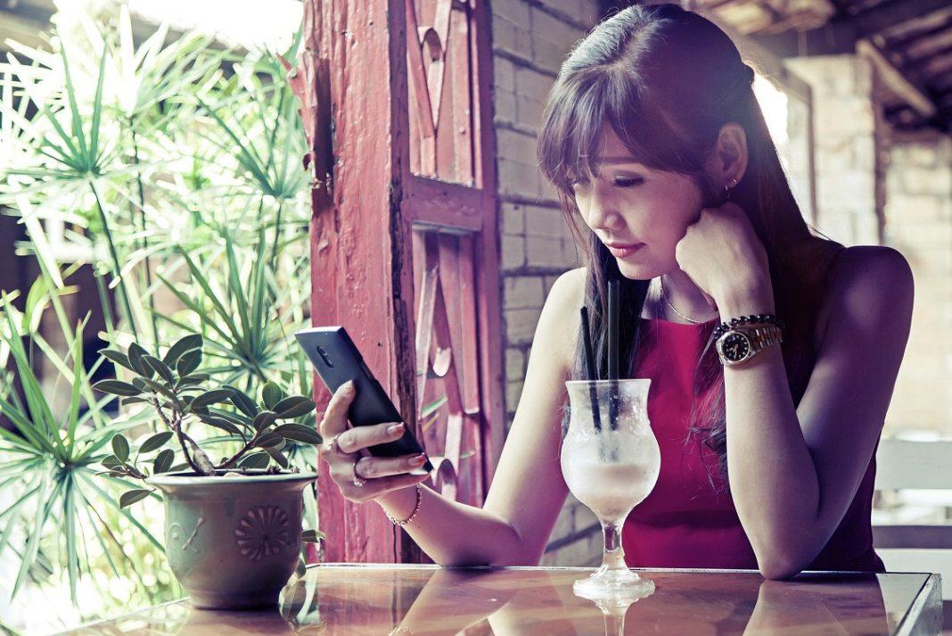 UNa chica mira su móvil mientras toma una copa