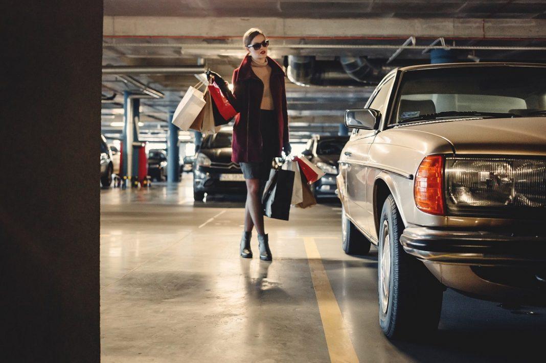 Imagen de una mujer con bolsas de la compra acercándose a su coche estacionado