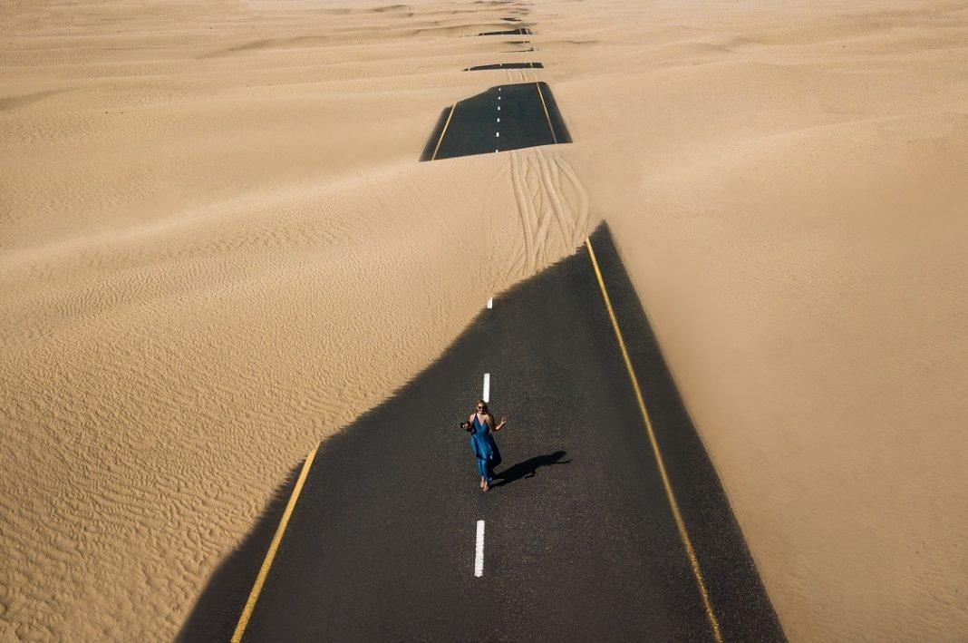 Imagen de una carretera cubierta parcialmente de arena