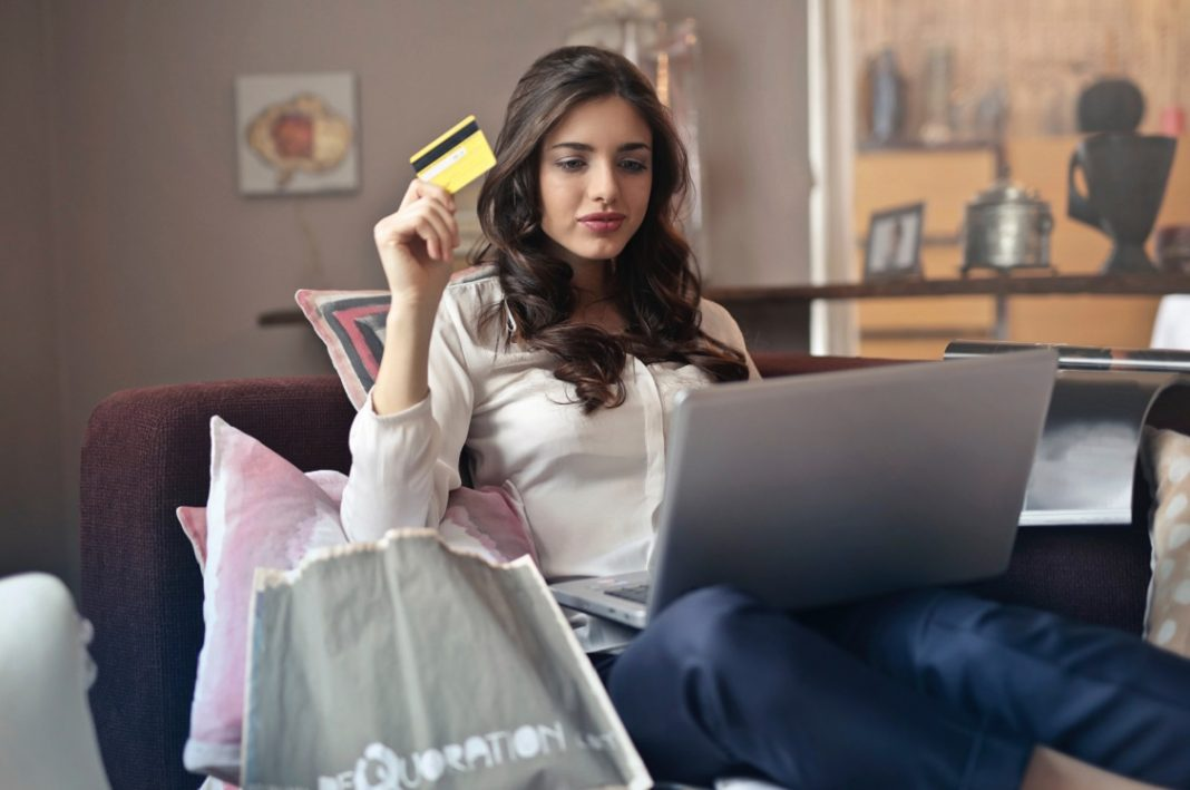 Mujer sentada sobre un sofá, utilizando un portátil y sujetando con la mano una tarjeta de crédito