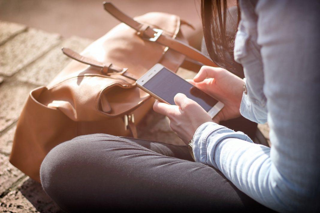 Persona sentada en el suelo consultando el móvil