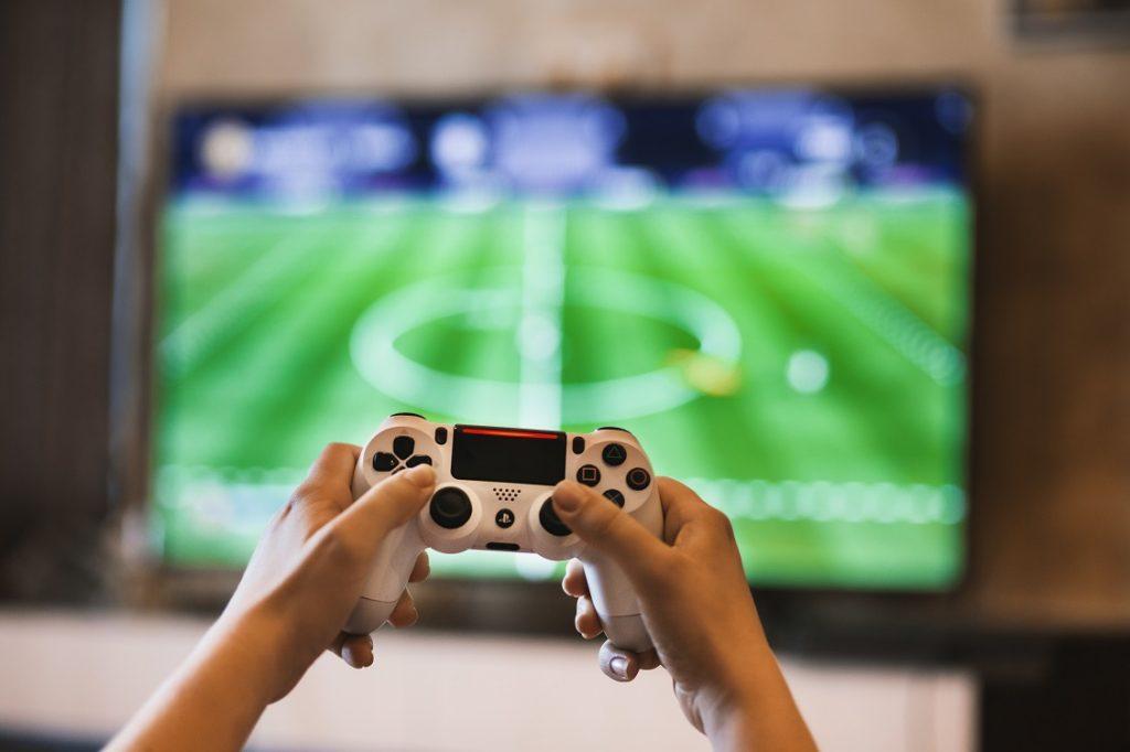 Persona jugando a un juego de fútbol en una videoconsola