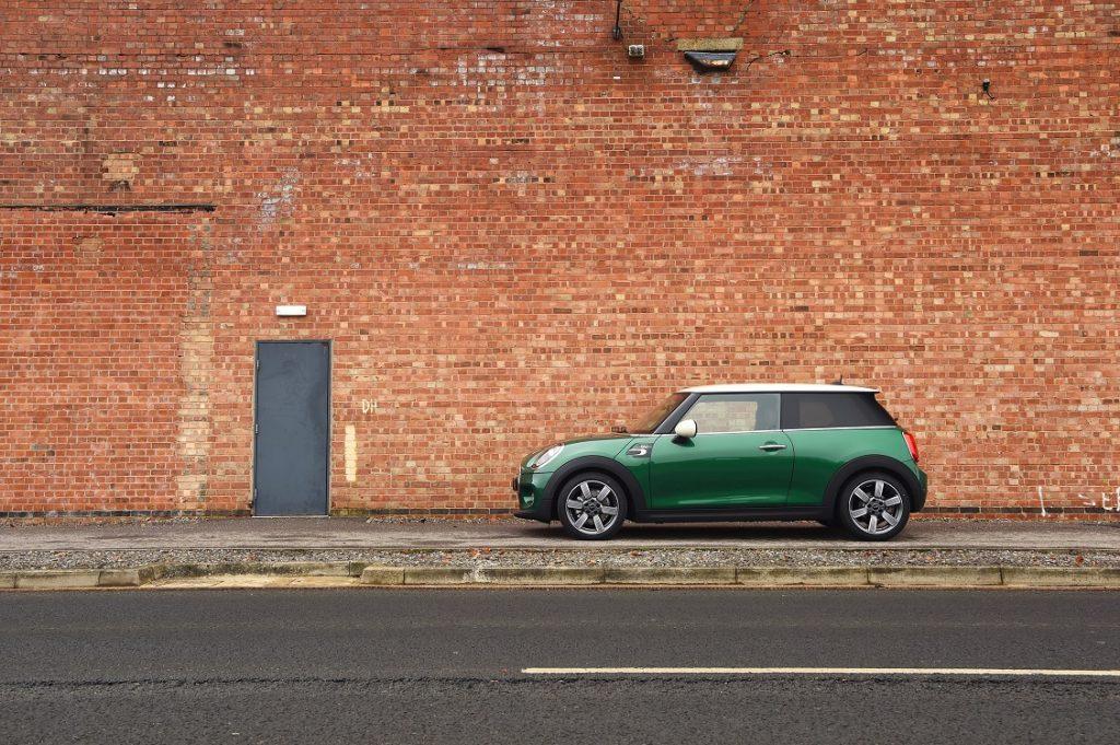 Imagen de un Mini de perfil frente a una pared de ladrillo