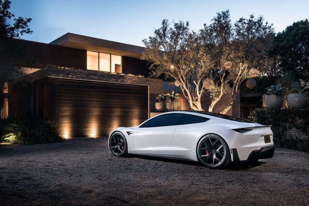 Tesla Roadster de color blanco aparcado frente a una casa