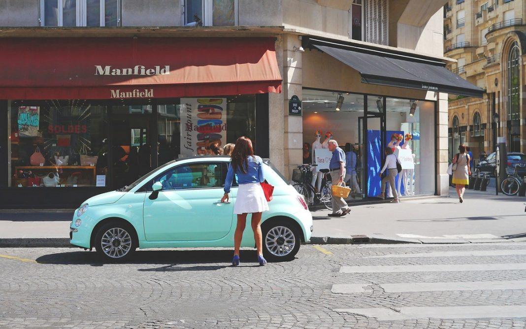 Imagen de una mujer aparcando un Fiat 500