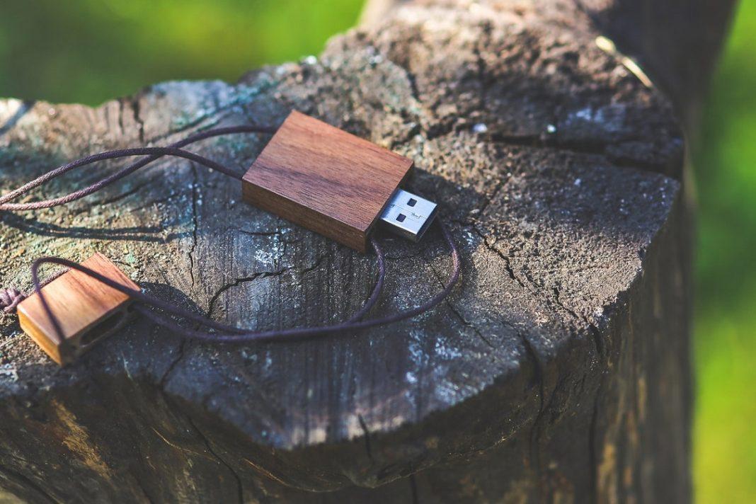 Pen drive con diseño similar a la madera, apoyado sobre un tronco cortado