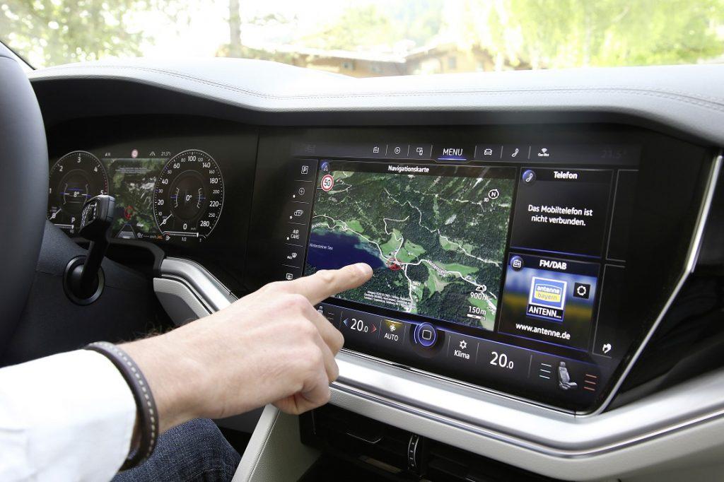 Detalle de una persona tocando con el dedo la pantalla del sistema multimedia del Volkswagen Touareg
