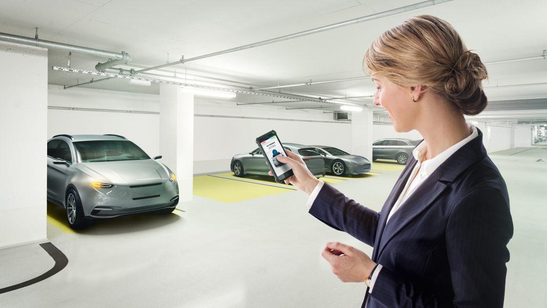 Mujer en un parking abriendo su coche a través del móvil