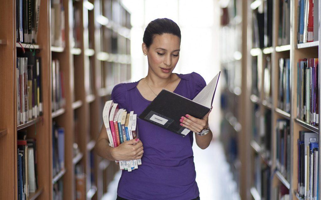 Imagen de una estudiante en una biblioteca