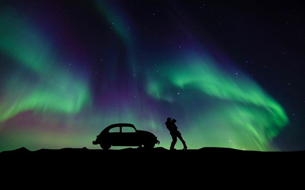 Imagen artística de una pareja con la aurora boreal de fondo