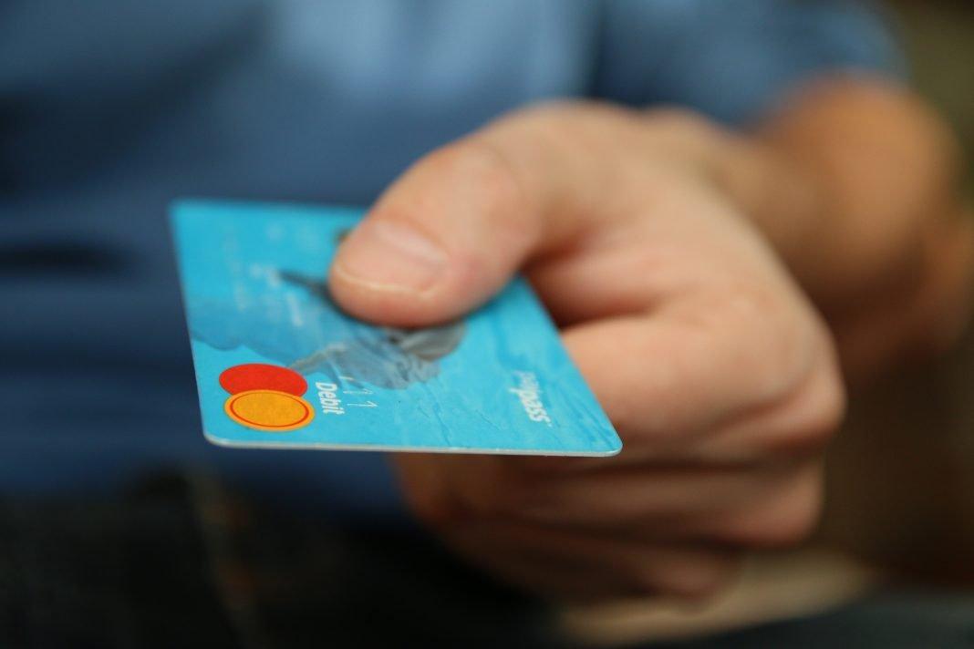 Primer plano de una tarjeta de crédito azul sostenida por una mano