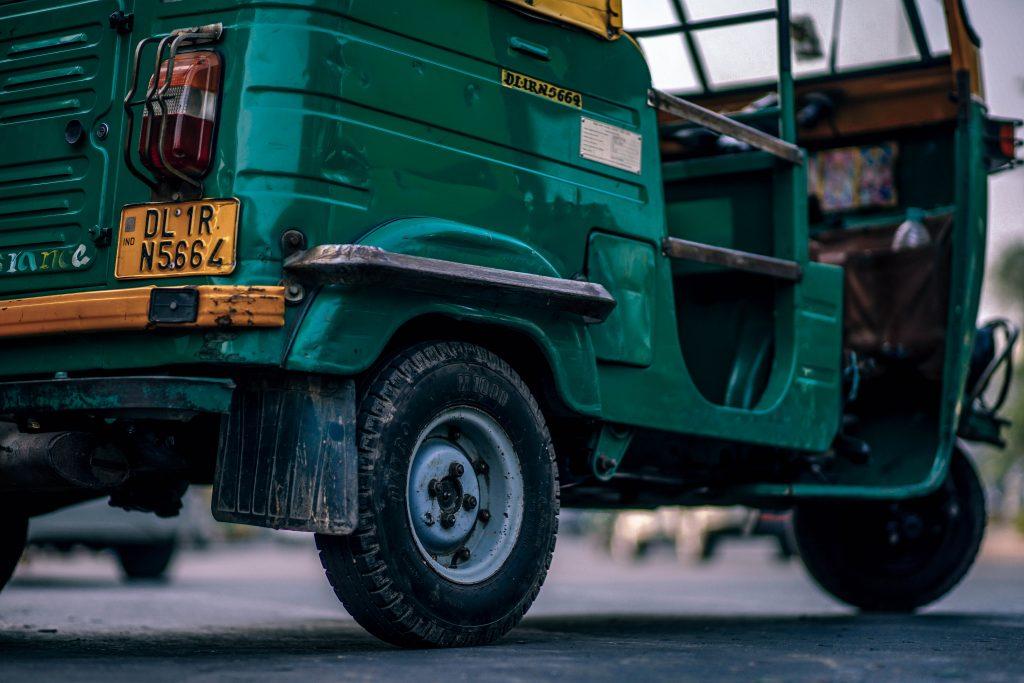 Un tuk tuk verde tradicional de la India en primer plano, en vista de tres cuartos trasera