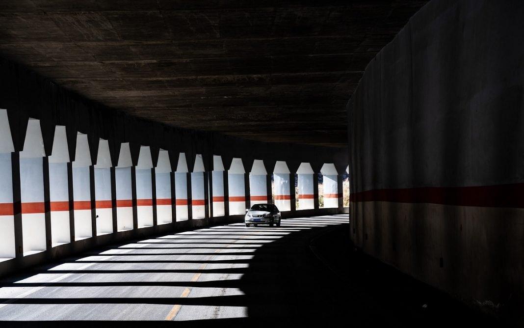 Imagen de un coche circulando por un túnel con luz.