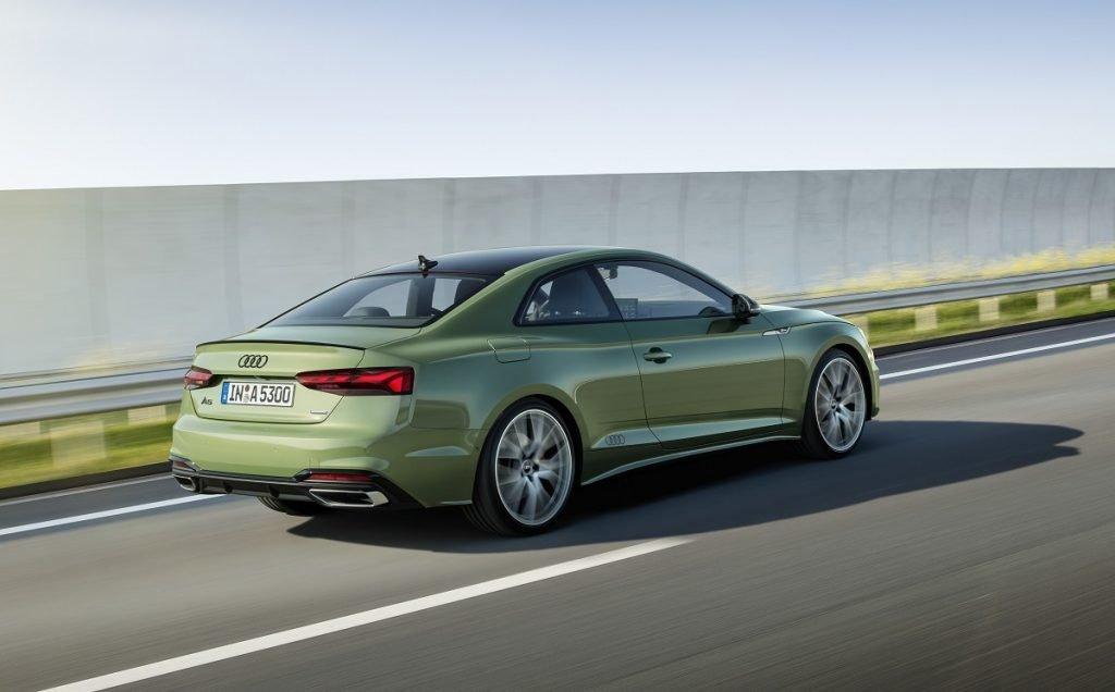 Imagen del renovado Audi A5 visto desde tres cuartos trasero y en color verde circulando por carretera