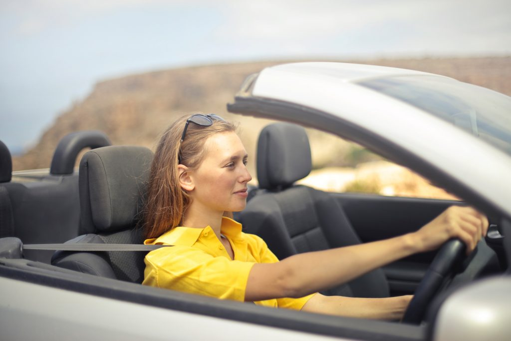 Mujer al volante de un descapotable