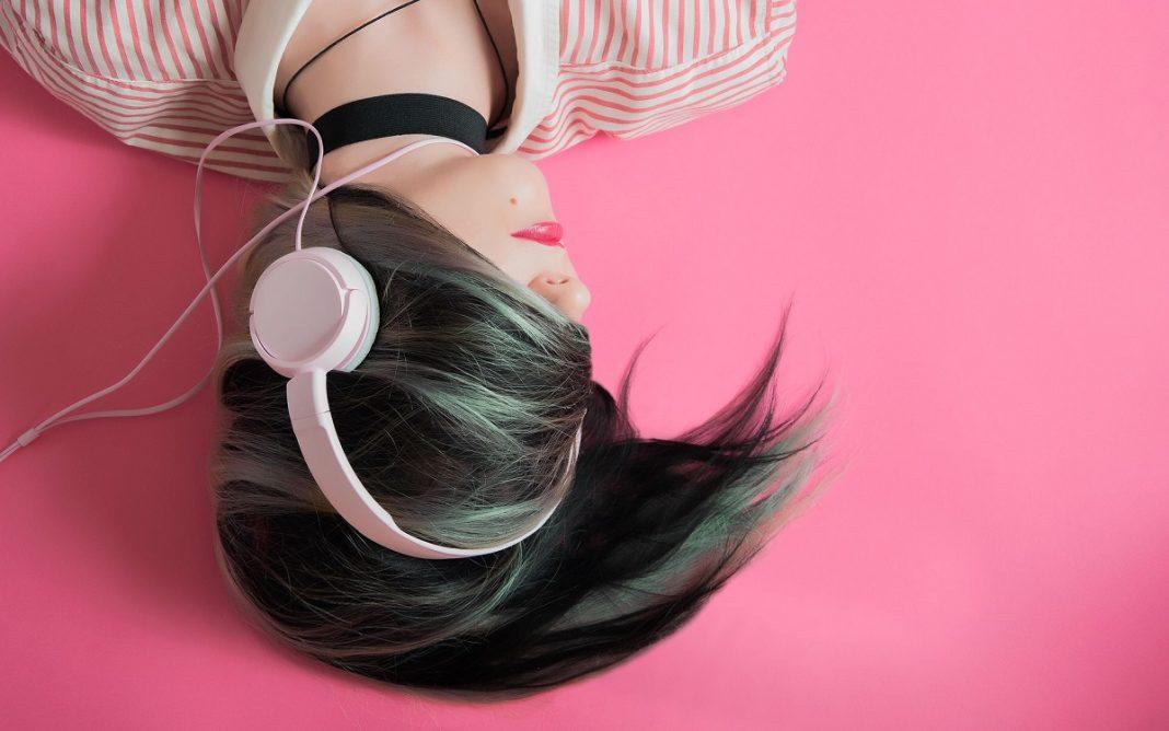 Imagen de una chica tumbada mientras escucha música con sus auriculares