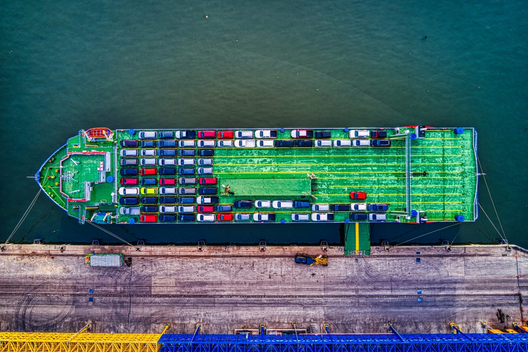 Un barco cargado de coches y atracado en un puerto visto desde arriba en un plano totalmente zenital