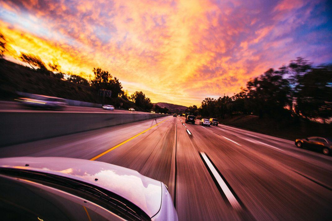 Vista del capó de un coche que circula por una autopista hacia el amanecer