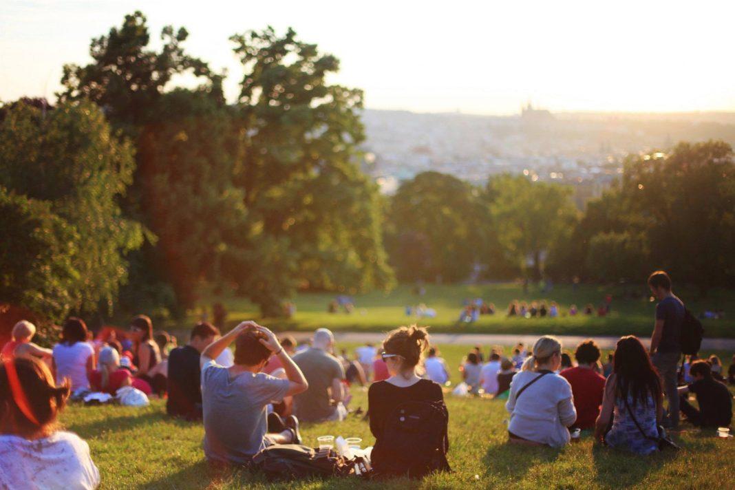 Explanada de césped en un parque llena de personas sentadas, disfrutando del atardecer